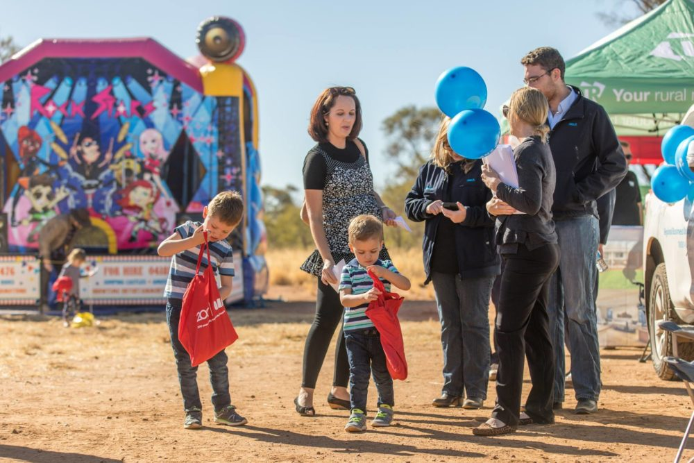 kids and parents holding balloons and talking at open day